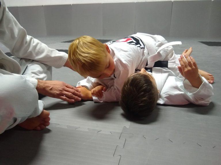Two children practicing Brazilian Jiu Jitsu technique