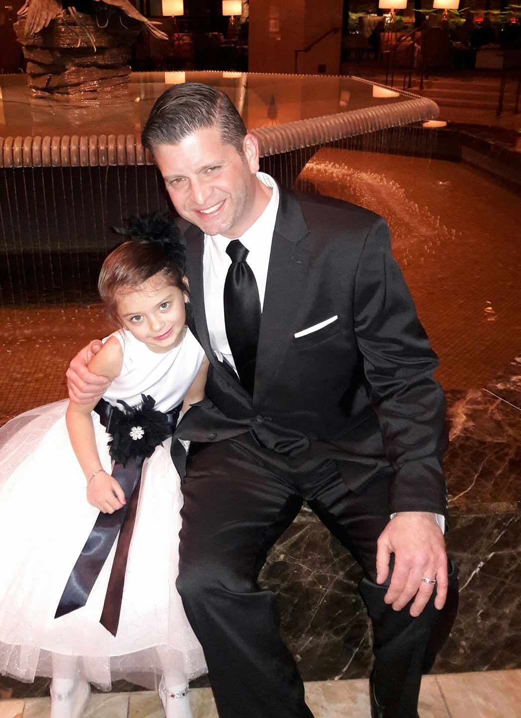 Man in black suit next to little girl
